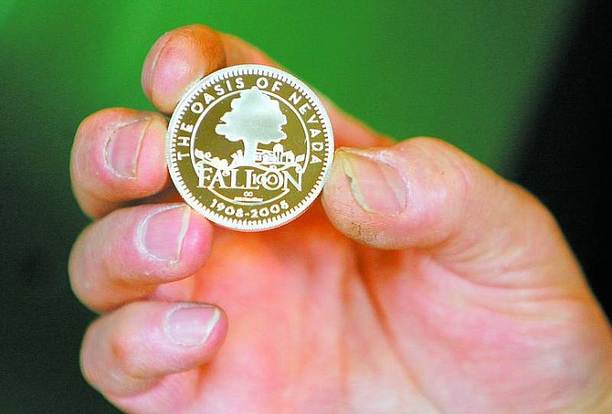 BRAD HORN/Nevada Appeal Ken Hopple, chief coiner for Coin Press No. 1 Carson City Mint, holds a limited edition of the city of Fallon Centennial silver coin at the Nevada State Museum on Friday.