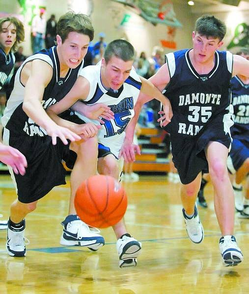 BRAD HORN/Nevada Appeal Carson's Markus Adams, center, battles Damonte Ranch players from left, Jake Johnson and Luigi Terrana during their game in Carson on Friday.