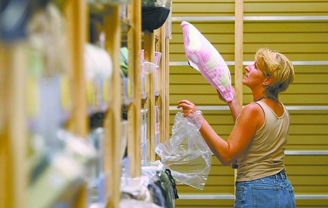 Cathleen Allison/Nevada Appeal Kathi Diehl stocks pillows in the home decor section of Burlington Coat Factory on Wednesday.