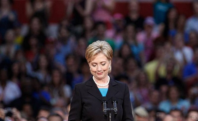 Ron Edmonds/Associated Press Sen. Hillary Rodham Clinton, D-N.Y., pauses as she is applauded at the National Building Museum in Washington on Saturday where she suspended her campaign for president.