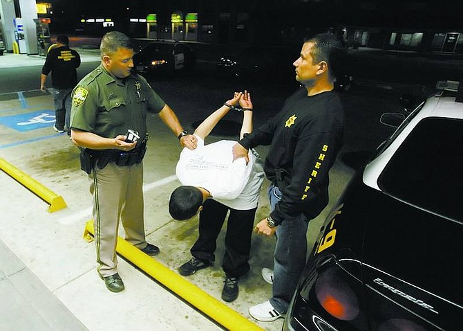 BRAD HORN/Nevada Appeal Carson City Sheriff's deputies Dan Ochsenschlager, left, K-9 Unit, and Sal Acosta attempt to test a suspect's alcohol level with a Breathalyzer at AM/PM on Carson Street Thursday. While Carson City's population continues to climb, the occurrences of crime in the city over the past decade shows a mixed bag, with no rate of any particular crime rising every year in the past decade.