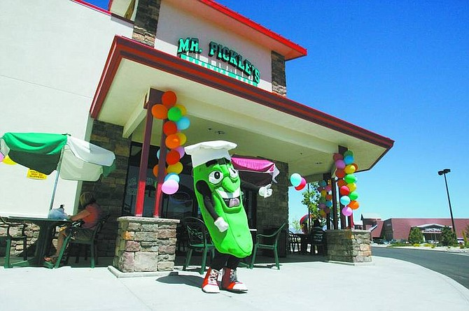 BRAD HORN/Nevada Appeal Erik Cruise, 17, plays air guitar in front of the Mr. Pickle's Sandwich Shop in Carson City on Friday afternoon.