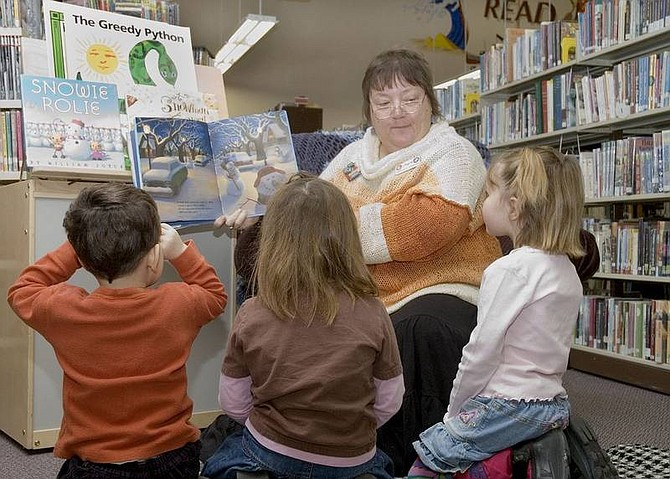 Christy Lattin/Nevada Appeal News Service Joyce Betts, the children's librarian at the Churchill County Public Library, reads a book to a small group of kids during story time. Enjoying the story, from left to right, are Brenton Baker, 3, Laura Smith, 4, and Lily Johnson, 5.