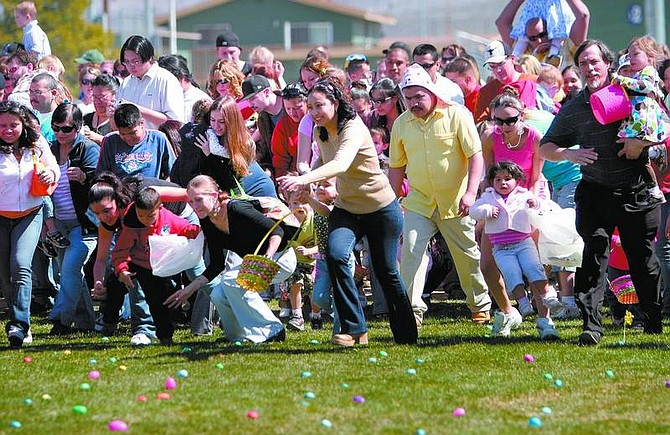 Amy Lisenbe/Nevada Appeal A large group of two and three year-olds and their parents dash from the starting line to hunt Easter eggs at Governor's Field Sunday afternoon.