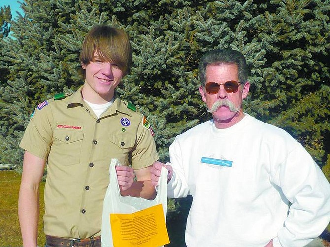 Submitted photo Tommy Dudley receiving a donation from Whit McGuinness. Tommy's Eagle Scout project was to collect toiletries for Advocates to End Domestic Violence.