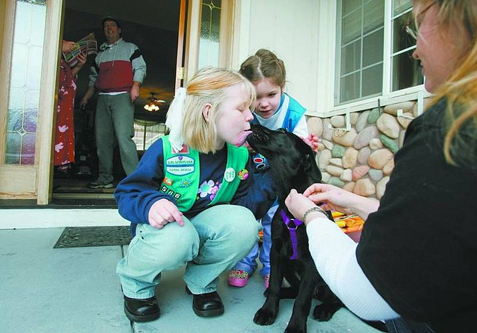 BRAD HORN/Nevada Appeal Scarlett McKee, a Junior Girl Scout from Troop 1566 of Carson City, gets licked by a black lab puppy, while Ansley Talafous, a Daisy Girl Scout from Troop 337, watches while the pair sells cookies in the Silver Oak neighborhood on Saturday morning. The girls are members of Carson City Service Unit 604.
