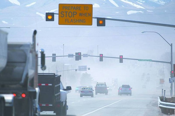 Traffic on Highway 50 East at Arrowhead Drive is seen through the dust and debris kicked up as high winds blew through Northern Nevada on Wednesday.  Cathleen Allison/ Nevada Appeal