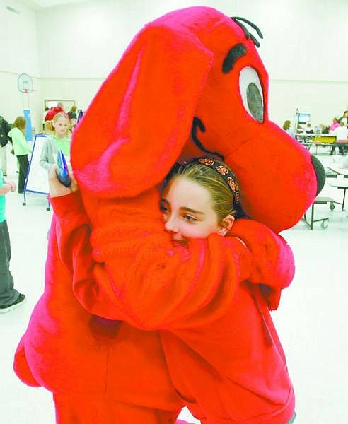 BRAD HORN/Nevada Appeal Stella Taylor, 9, a fourth-grade student at Riverview Elementary School in Dayton, gets a hug from Clifford at the school's Family Learning Night on Thursday.