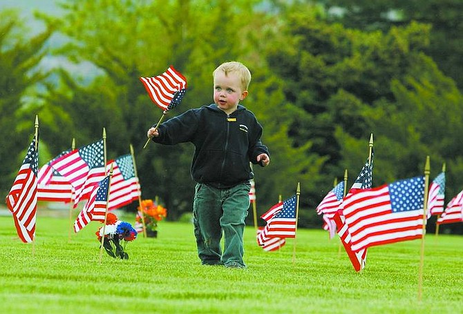 BRAD HORN/Nevada Appeal Nolan Pedersen, 2, of Carson City, helps place flags on veterans' graves at Lone Mountain Cemetery on Friday in preparation for Monday's Memorial Day ceremony.