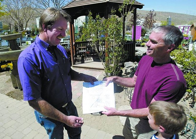 Steve Lang and his son Spencer, right, hand over their latest puzzle to Dave Ruf, owner of the Greenhouse Garden Center in Carson City on Sunday afternoon. Entries will be available beginning today at the Greenhouse Garden Center and at Lang's Web site, www.scholarpuzzle.wordpress.com.      Amy Lisenbe/Nevada Appeal