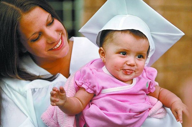 Cathleen Allison/Nevada Appeal Silver State Charter High School graduate Brittany Parra holds her 6-month-old daughter Destiny Grace Ledford after graduation Tuesday night at the Community Center.