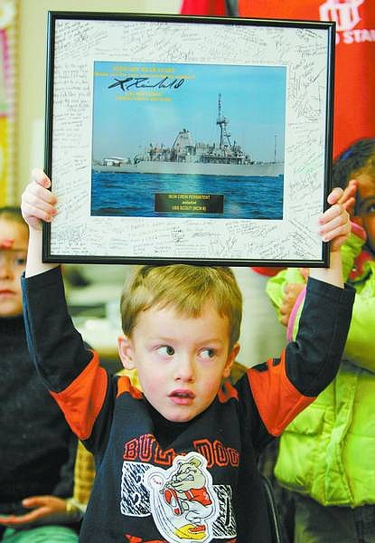 BRAD HORN/Nevada Appeal Auryn Deem, 4, displays a picture of the USS Scout that is signed by the crew at the Head Start school in Carson City on Friday. Deem and the rest of his classmates have been corresponding with the crew for the past two years.