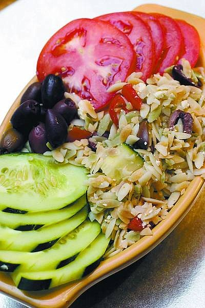Larry Crowe/Associated Press A delicious and attractive salad, Mediterranean orzo salad, fits in well with a meal from the grill as seen here.