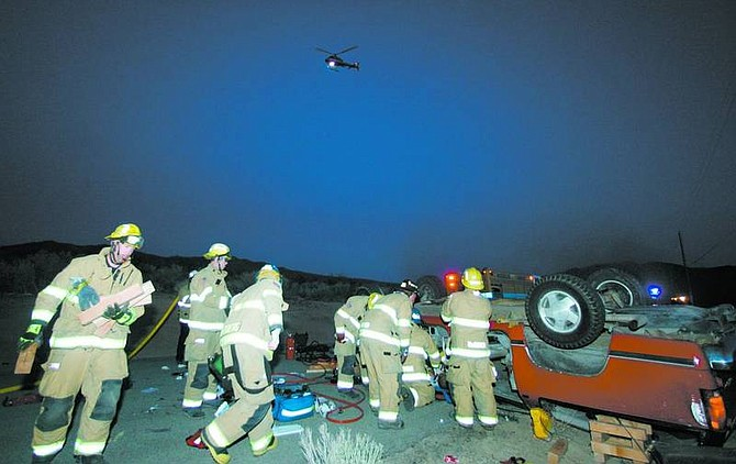 BRAD HORN/Nevada Appeal Carson City firefighters work to extract a victim from a GMC Suburban on Sunday evening after it flipped three times on Golden Eagle Lane while it was traveling north. A man who was ejected from the vehicle is in the Care Flight helicopter above.