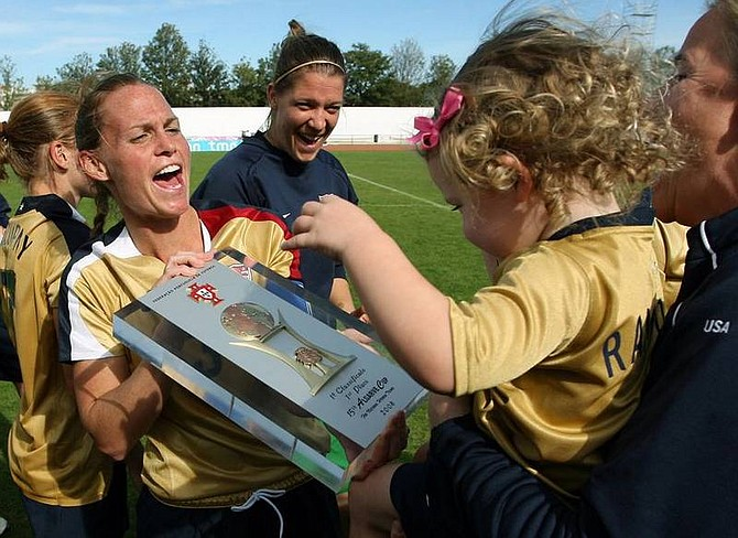 AP Photo/Steven GovernoUSA women's national soccer team player Christine Rampone, left, holds up the Algarve Cup trophy for a baby to see after their 2-1 win over Denmark in the final match Wednesday, March 12, 2008, at Vila Real de Santo Antonio's stadium, in the Algarve, Portugal.