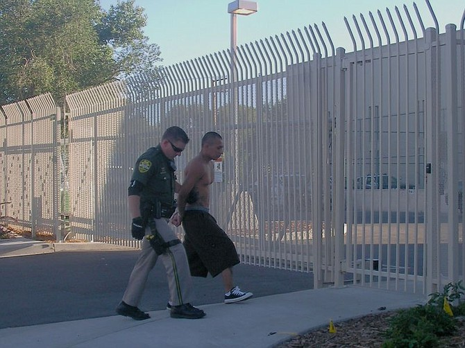 A Carson City deputy walks Ricardo Llamas into the jail this afternoon. Llamas and John Turner, both 19, were arrested on suspicion of attempted murder in connection with a shooting at a Woodside Drive apartment complex early Saturday morning
