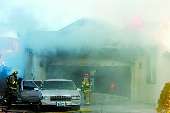 Carson City Firefighters work to extinguish a fire at Wayne O'Malley's home at 2455 Chardonnay Drive on Saturday.   BRAD HORN/Nevada Appeal