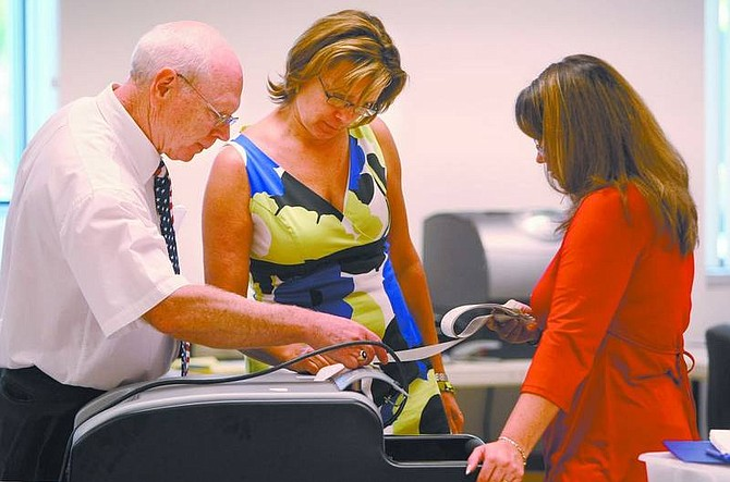 Cathleen Allison/Nevada Appeal Carson City Clerk/Recorder Alan Glover, Chief Deputy Elections Clerk Sue Merriwether and elections Deputy Clerk Sylvia Yasumoto work to tally votes Tuesday night.