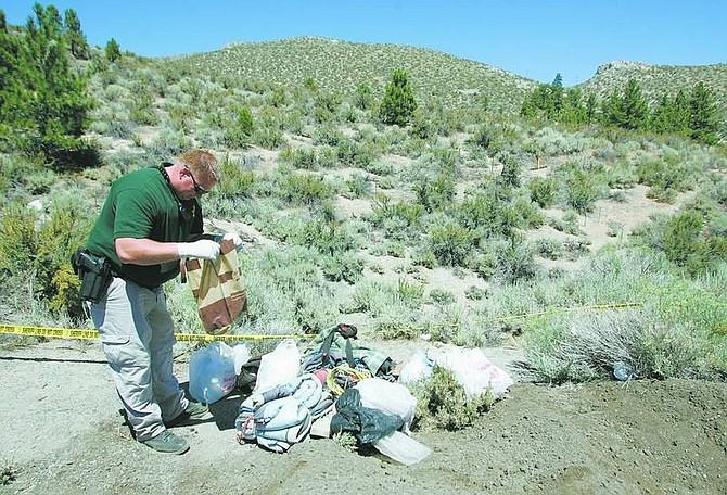 BRAD HORN/Nevada Appeal Carson City Sheriff's deputy Sam Hatley looks through a bag found near a dead body that was discovered in a ditch along Hwy 50 near Spooner Summit on Sunday.