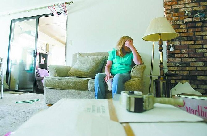 BRAD HORN/Nevada Appeal Kathy Brisby takes a break from packing at their east Carson City home on Friday afternoon. Lena Brisby, Kathy's mother, who has lived at the home for 20 years, has to be out by the end of the month.