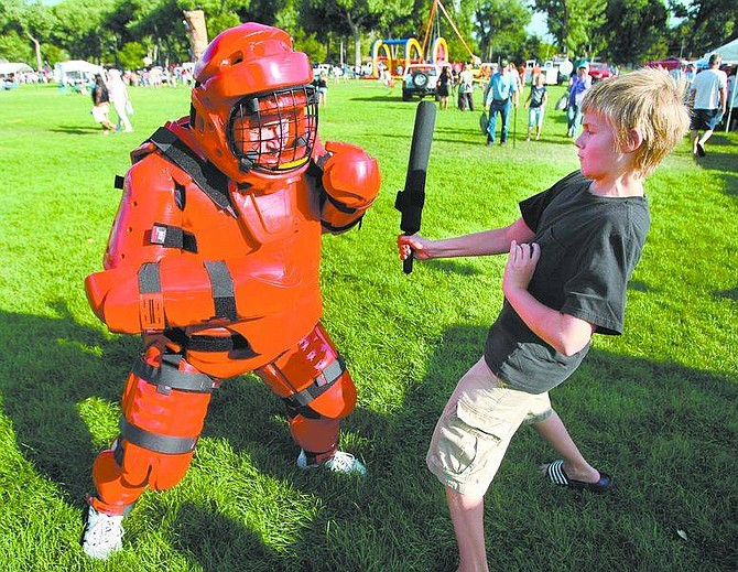 Cathleen Allison/Nevada Appeal  Kieran Henderson, 12, takes a few swings at Legislative Police Officer Nick Gillen, who wore a defensive tactics training suit during Tuesday's National Night Out event at Mills Park. For more photos visit www.nevadaappeal.com and click on photos and videos.