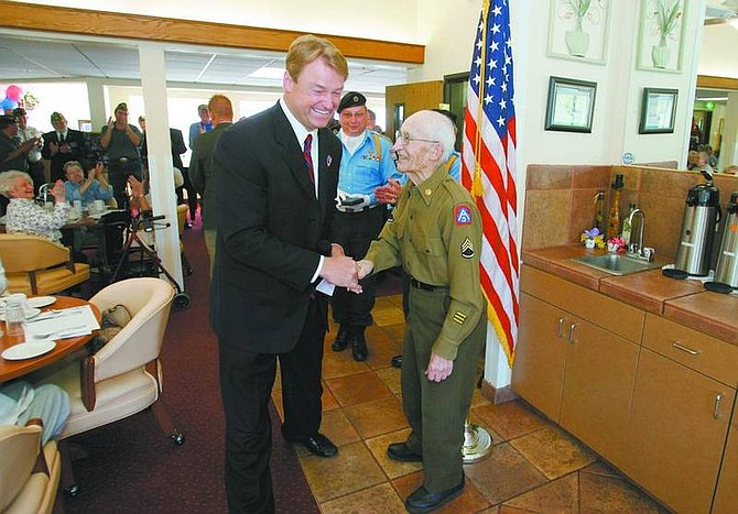Al Porter greets U.S. Rep. Dean Heller, R-Nev., before receiving his Purple Heart at the Carson Plaza Retirement Home Saturday. Porter served in the U.S. Army during World War II and fought during the Battle of the Bulge.    BRAD HORN/Nevada Appeal