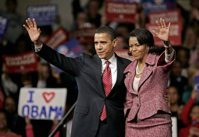 Steven Senne/Associated Press Democratic presidential hopeful, Sen. Barack Obama, D-Ill., left, and his wife, Michelle, right, wave as they step off the stage after a rally, in Columbia, S.C. Saturday.