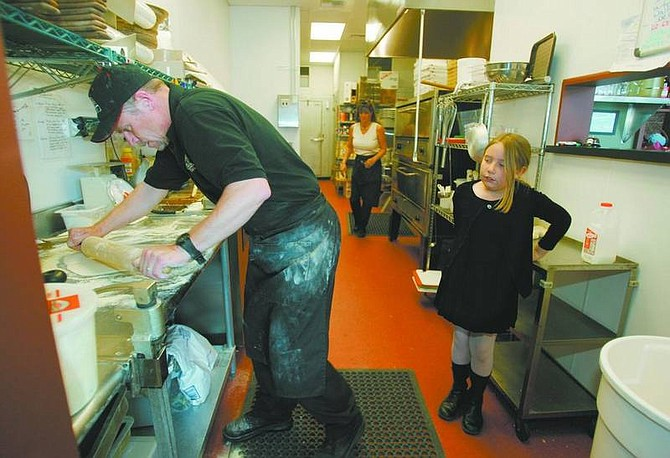 BRAD HORN/Nevada Appeal Troy McDonald rolls pizza dough at Brugo's Take-n-Bake Pizza Bistro at lunchtime while his daughter Sarah, 9, watches and wife Chris works on Wednesday.