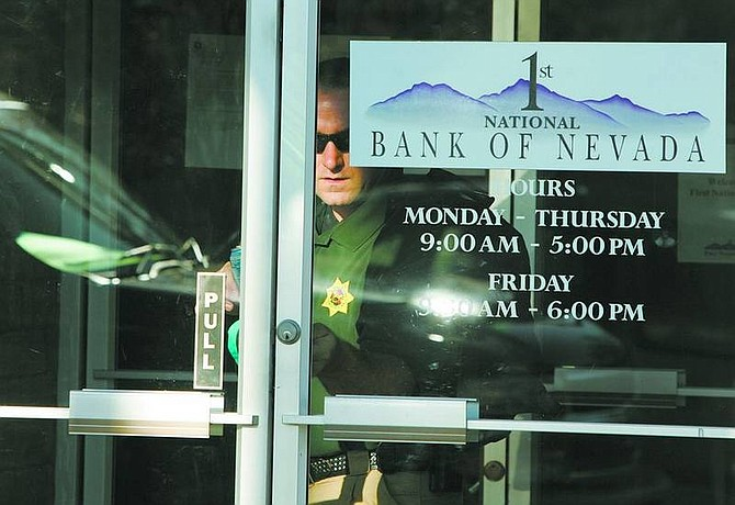 Brad Horn/Nevada AppealCarson City Sheriff's detective David LeGros locks the door at 1st National Bank of Nevada on Friday after federal regulators closed the bank in Carson City, Nev.