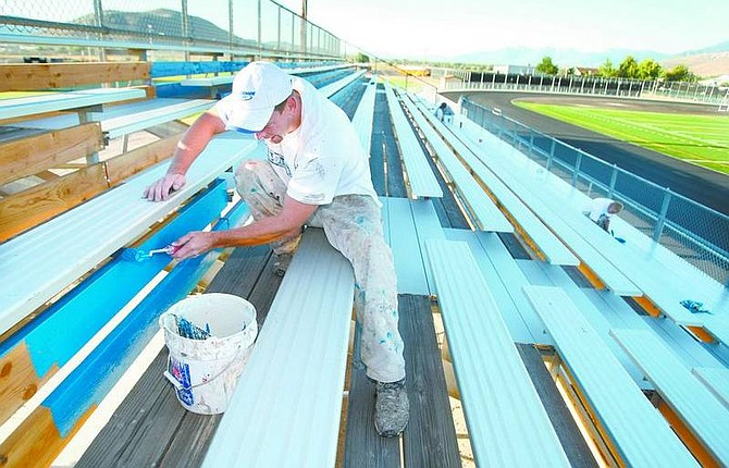 Cathleen Allison/Nevada AppealPaul Tim and a painting crew from Sunridge Painting, of Minden, puts the finishing touches on the bleachers at the Carson High School stadium Thursday morning. The $2 million project to renovate the facility, including a new track and FieldTurf football field, will be unveiled tonight when the Senators play their season opener against Spanish Springs at 7 p.m.