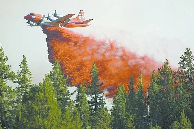 Jonah M. Kessel /Nevada Appeal News ServiceAn aircrfaft drops fire retardant on the Burnside fire in Hope Valley. Several Hope Valley businesses and homes are being threatened by the 100-acre fire along Blue Lakes Road about a mile south of Highway 88 in Alpine County south of Lake Tahoe, Calif.