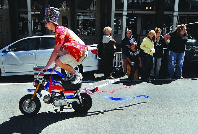 Kevin Clifford/Nevada AppealMatt Potts of Reno rides a mini-motorcycle doing tricks and handing out candy during Virginia City Labor Day Parade on Monday.