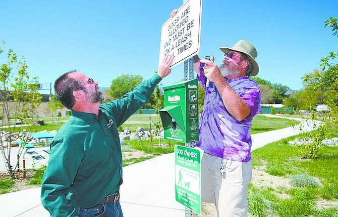 Cathleen Allison/Nevada AppealCarson City Parks workers Steve Mariolo, left, and Steve Crawford install signs at the Ronald W. Wilson Memorial Park on Wednesday. The new five-acre park, at Mark and James ways, will open to the public Friday.
