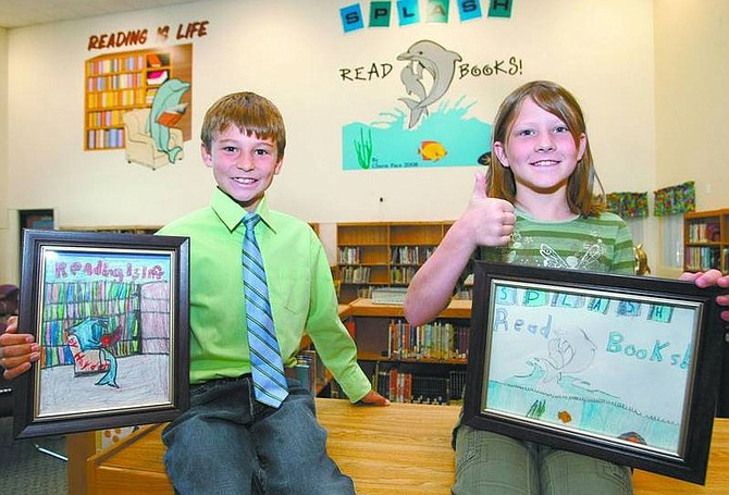 Cathleen Allison/Nevada AppealBordewich-Bray Elementary students Hayden Story, 8, and Cherie Pace, 10, show off their winning artwork at the library. More than 600 students participated in the contest to create reading-related art for the library walls and student votes determined the winners. During the summer break, Sign Pro transferred the drawings to walls.