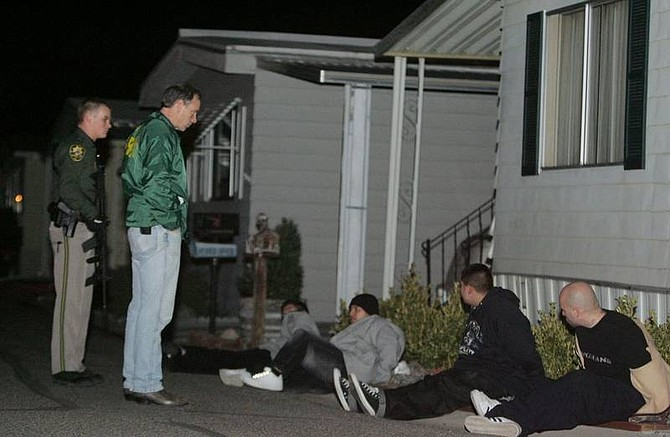 Brad Horn/Nevada Appeal Carson City Sheriff Kenny Furlong questions suspects that were pulled over after entering the Comstock Mobile Home Park after a car carrying four males that shot toward Carson City Sheriff's Dep. Gary Underhill tried to evade police in the 2600 block of College Parkway on Saturday evening.