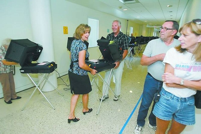 BRAD HORN/Nevada Appeal Sue Merriwether, chief deputy clerk, and Bob Sanders carry a voting machine with a broken screen, from the voting area at the Clerk-Treasurer's office on Saturday morning during early voting in Carson City.