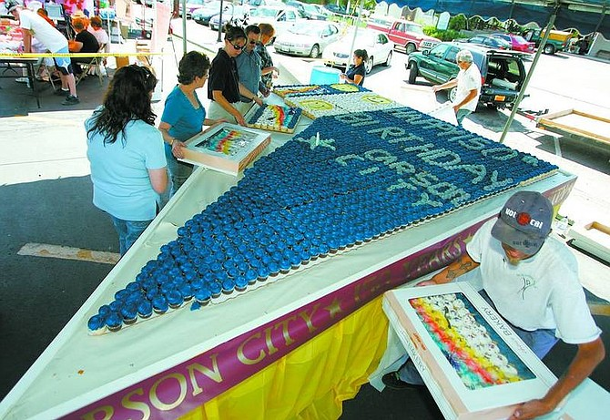 BRAD HORN/Nevada Appeal Walmart employees and volunteers get the cake ready for the ribbon-cutting in the Nugget parking lot during sesquicentennial activities on Saturday.