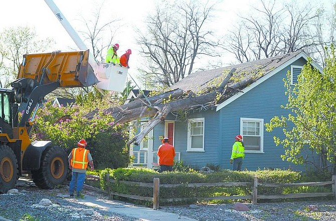 Cathleen Allison/Nevada Appeal Carson City Public Works crews remove a fallen cottonwood tree from a house at E. Telegraph and Anderson streets Tuesday afternoon. An official on scene said the estimated 60-foot tree was rotten in the middle, making it susceptible to Tuesday's high winds. No one was home at the time.