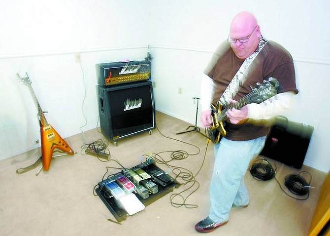 BRAD HORN/Nevada Appeal Tom Rhodes, owner of Bumperland Recording Studio, plays guitar at his Carson City studio on Wednesday.
