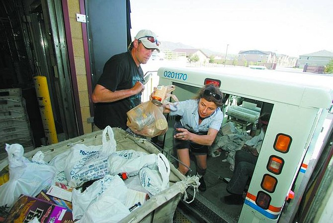 BRAD HORN/Nevada Appeal Carrier Kathleen Michael unloads donated food while FISH volunteer Peter Wagner assists at the Carson City Post Office on Roop Street Saturday during the annual letter carriers' food drive.