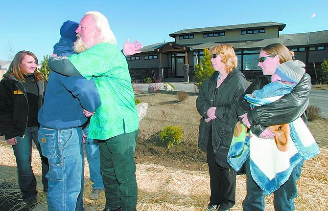 Amy Lisenbe/Nevada Appeal Steve Boettcher, center, receives a hug Saturday morning from Brian Barker of Sierra Earthworks, a Reno business. Cynthia Osborn, sales and marketing manager and community relations for West Haven Development Group, also based in Reno, is watching from the left. Mary Boettcher, her daughter Stephanie and 18-month-old grandson Joshua are standing on the right. All are in front of the new 2,700-square-foot Boettcher home in Stagecoach.