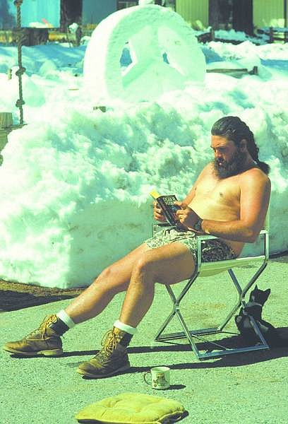 Tahoe Daily Tribune File Photo After a hard day shoveling snow from his South Lake Tahoe driveway, Scott Delvecchio takes time out with his cat to relax in the sun with a good book in this March 28, 1991, photo. In the background is a peace sign Delvecchio sculpted earlier that day.
