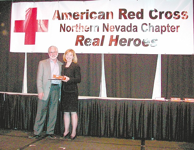Special to the Nevada AppealNevada Appeal publisher Niki Gladys presents Steven Saylor with the Red Cross Real Heroes award for his and wife Johnye's animal rescue work Thursday at Harrah's Reno. The Nevada Appeal was a sponsor of the event that honored Northern Nevadans for acts of heroism large and small.