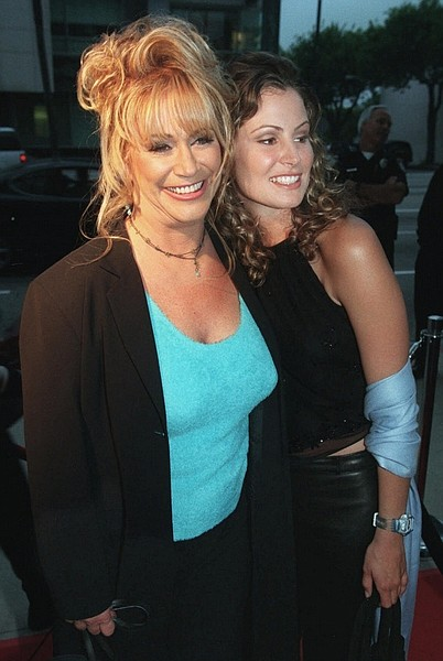 "FILE - In this April 27, 2000, file photo adult film legend Marilyn Chambers, left, poses with Tracy Hutson, the actress who portrays her in the Showtime film ""Rated X,"" at a screening of the film at the Academy of Motion Picture Arts & Sciences in Beverly Hills, Calif. Chambers was found dead by her 17-year-old daughter at her home in northern Los Angeles County on Sunday, April 12, 2009, according to her friend Peggy McGinn. She was 56. The cause of death has not been determined. (AP Photo/Chris Pizzello, file)"