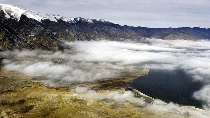 ** ADVANCE FOR SUNDAY, APRIL 26 ** FILE  - This Jan. 28, 2004 file aerial photo shows the receding shoreline, lower left, of Walker Lake near Hawthorne, Nev., The lake has been dying a slow death for more than a century, choked by drought, agriculture and evaporation. Hawthorne's Loon Festival has been canceled in 2009, replaced instead by an education day April 25 to bring awareness to Walker Lake's teetering ecosystem and ongoing, multimillion dollar and multifaceted efforts to save it from a salty demise.  (AP Photo/Cathleen Allison, File)