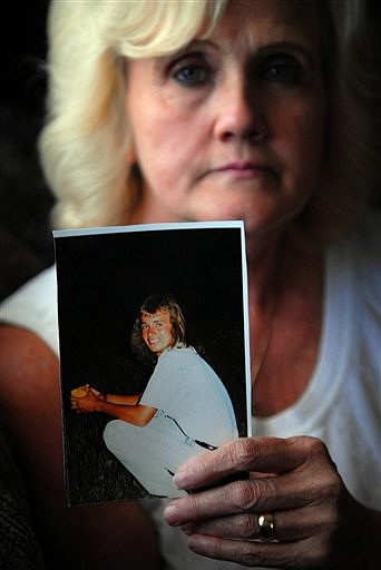 FILE - This Sept. 12, 2007 file photo shows Marge Shipley holding a photograph of her son Carl Lackl, Jr., 38, who was fatally shot in front of his house in July. It is believed that he was killed to prevent him from testifying in a Baltimore City homicide trial in which he was the key witness. Authorities say Lackl was gunned down after the suspect ordered the hit from a cell phone behind bars. State officials appealed to members of Congress on Wednesday to give states a new tool to control illegal cell phone use by prison inmates and quickly ran into protests from the phone industry. (AP Photo/Baltimore Sun, Chiaki Kawajiri, File) **MANDATORY CREDIT, NO SALES,  BALTIMORE EXAMINER AND WASHINGTON EXAMINER OUT**