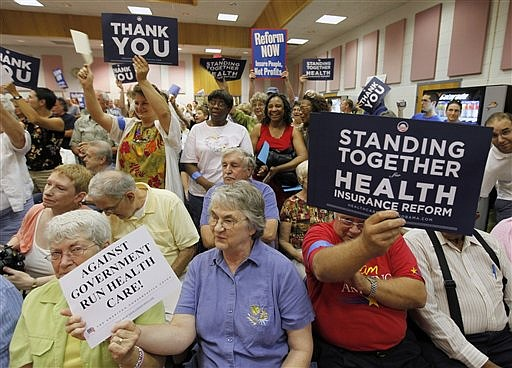 Constituents of Congressman Tom Perriello, D-Va., holds signs as they listen to the congressman during a town hall meeting on Health Care at the Fluvanna Middle School in Fork Union, Va., Monday, Aug. 17, 2009.  Perriello is one of three dozen Democratic Freshmen that have been thrown into the center of one of the most contentious policy debates in years. (AP Photo/Steve Helber)