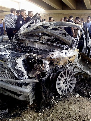People gather around a destroyed car after a suicide car bomber targeted a checkpoint in Ramadi, 115 kilometers (70 miles) west of Baghdad, Iraq, Monday, Sept. 7, 2009. The car exploded as vehicles were waiting to be inspected before crossing a bridge near the provincial capital of Ramadi, a police officer said. The dead included three police officers; the others were civilians, police said. (AP Photo)