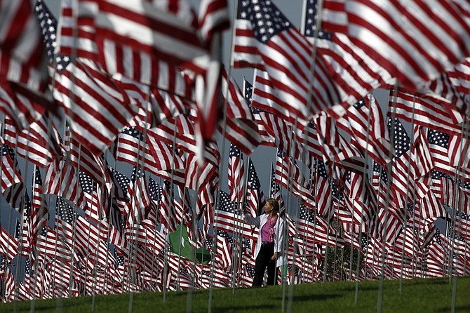 Marnie Mitze, from Pepperdine University, walks among thousands of American flags at a memorial honoring the victims of the Sept. 11, 2001 terrorist attacks, set by volunteers at the campus lawn in Malibu, Calif. on Friday, Sept. 11, 2009. One flag for each of the nearly 3,000 lives lost on that tragic day. The installation of the flags be on display Sept. 11 to 18. (AP Photo/Damian Dovarganes)
