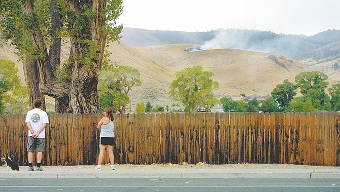 Bystanders on Ormsby Boulevard watch a lightning fire burn off Kings Canyon Road.